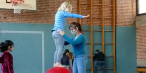 Ein Mädchen balanciert mit Hilfe auf einer roten Kugel. Im Hintergrund übt ein Junge auf einer Rolla-Bolla.