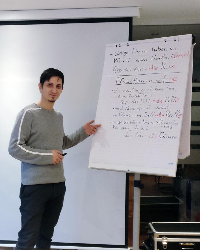 Thomas Lubecki steht vor einer seiner Flipcharts, mit welchen er seinen Deutschunterricht veranschaulicht.